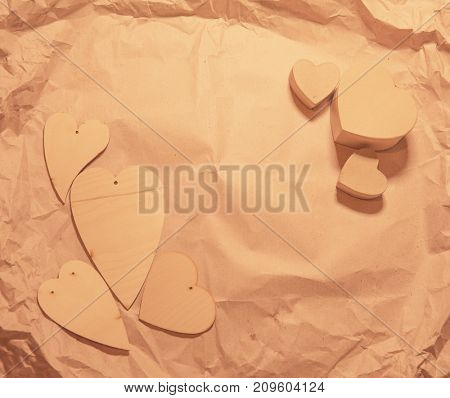 Wooden hearts on crumpled craft paper