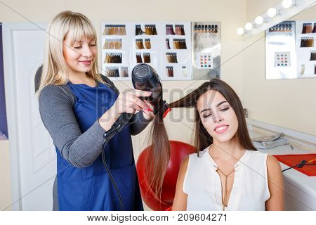 Beautiful young woman reading magazines at the barbershop and a professional female barber drying her healthy hair on a blurred background.