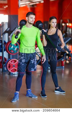 Man and woman in the gym posing on the camera with a hammer in their hands. Concept of a healthy lifestyle.