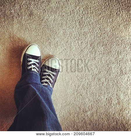 a person wearing sneakers standing on carpet.