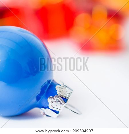 Close-up of xmas blue ball with blurred colorful Christmas decor in background. Christmas and New Year concept with copy space. Christmas greeting card.