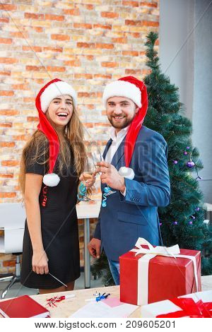 Confident bearded man in a Santa cap and happy, gorgeous woman with a glass of wine celebrating Christmas on a blurred festive background.