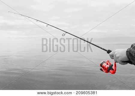Hands of a fisherman with a red spinning rod with the line with a line on a motor boat in the lake on a cloudy day
