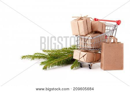 Shopping trolley with gift boxes and brenches of fir-tree on a white background. Christmas and New Year sale.