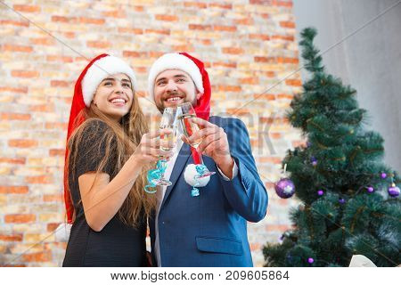 Fantastic positive romantic couple in cute Santa hats celebrating New Year or Christmas with alcohol in fancy glasses on the blurred background.