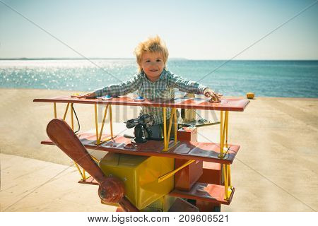 Little Pilot, Game On Seashore. Little Boy Play Different Games On Beach. Helicopter On Beach During