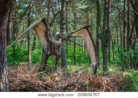 Life sized Pterodactyl dinosaur statue in a forest