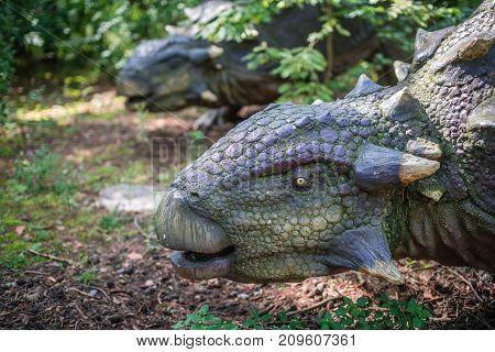 Life sized ankylosaurus dinosaur statue in a forest