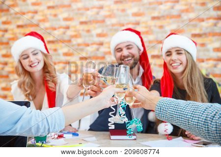 Close-up of clinking glasses of alcoholic drinks and happy friends celebrating Christmas or New Year in Santa caps on a blurred background.