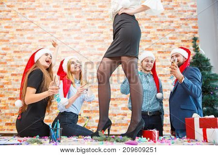 Close-up picture of long, beautiful woman's legs standing on the table and happy friends in santa caps on a festive Christmas background.