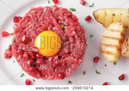 Delicious steak tartare with yolk, pomegranate seeds and potatoes on plate