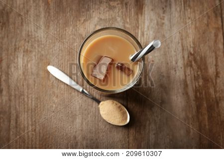 Glass with protein shake and powder in spoon on wooden table