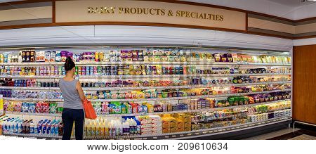 BANGKOK THAILAND - OCTOBER 13: Female customer shops in the dairy section of Foodland Supermarket in Victoria Garden in Bangkok on October 13 2017.