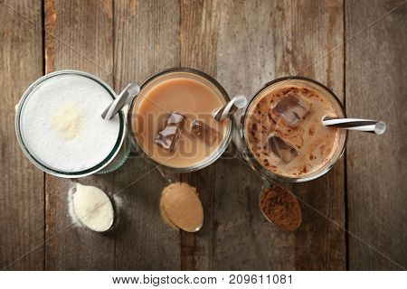 Glasses with different protein shakes and powders in spoons on wooden table