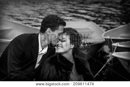Sensual black and white portrait of happy kissing couple against the blurred background of a lake with boats. Selective focus.