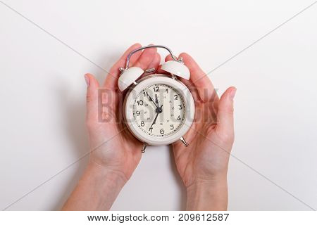Classic Alarm Clock in a hand. Concept anyone with time on hand equal. At 12 o'clock