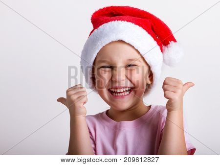 portrait of a smiling woman in santa hat. shows thumbs up