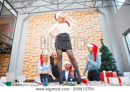 Sexy business lady drinking alcohol and dancing on table next to office friends in Santa hats on a Christmas party on the festive background.