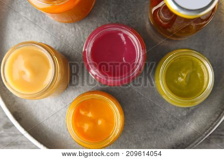 Assortment of jars with tasty baby food on plate