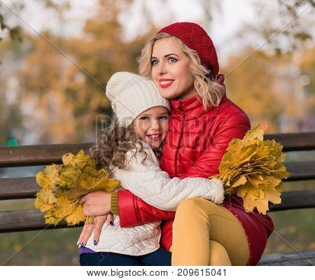 Happy family in colorful autumn park. Mother and daughter playing outdoors in the park and enjoying the beautiful autumn nature. love, relationships, season and family concept