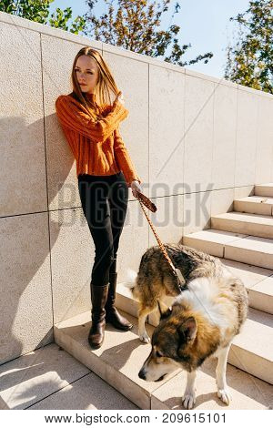 beautiful girl in an orange sweater and boots stands with her dog and looks away