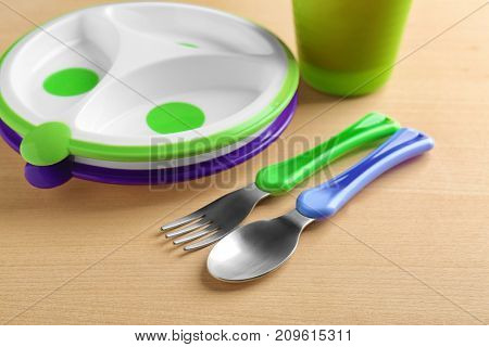 Bright baby dishware and eating utensils on table