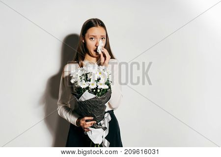 the girl is allergic to flowers. The girl covers her nose with a napkin. Allergy, sick girl