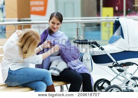 Young European Gay Couple Or Friends Women With Baby Sitting On A Bench Close To White Baby Carriage