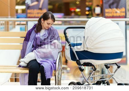 Young european woman with violet stole is breastfeeding her little child close to white baby carriage at public place shopping mall at day time