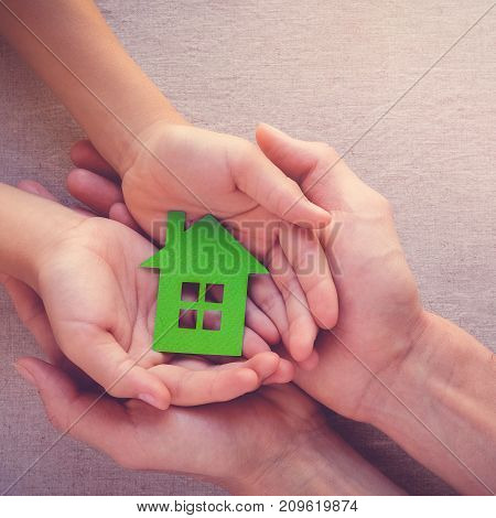 Adult and child hands holding paper eco house family home homeless shelter and real estate concept
