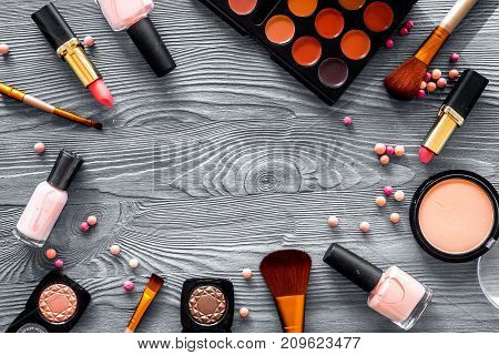 visagiste work table with decorative cosmetics of beige and nude tones set on grey wooden background top view mockup
