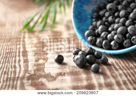Fresh acai berries scattered from bowl on wooden table