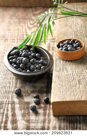 Bowls with fresh acai berries on wooden table