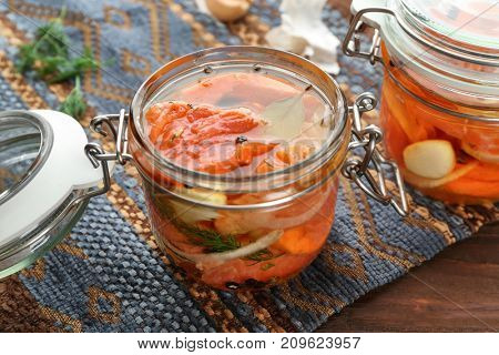 Jar with delicious marinated salmon on table