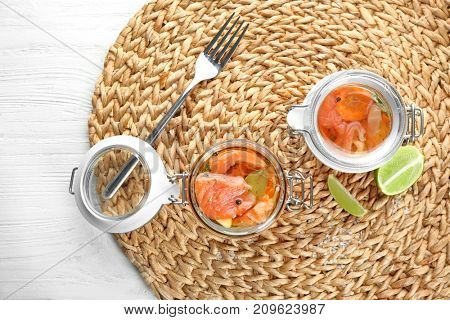 Jars with delicious marinated salmon on wicker mat