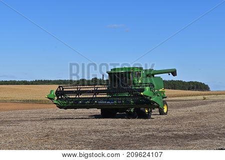 PELICAN RAPIDS, October 3, 2017: The green self propelled combines in the autumn residue of a soybean field is product of John Deere Co, an American corporation that manufactures agricultural, construction, forestry machinery, diesel engines,, and drive t