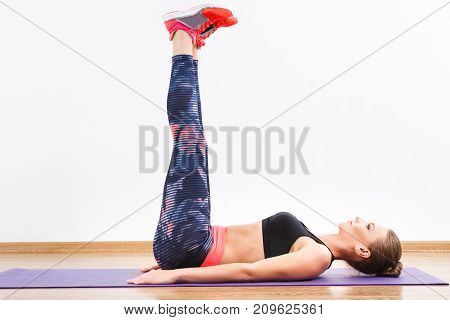 Beautiful Girl Doing Physical Exercises On Mat At Gym