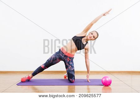 Pretty Girl Doing Physical Exercises On Mat At Gym