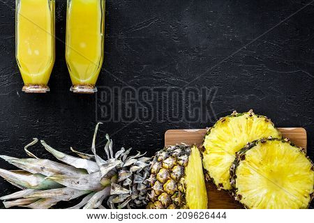 Tropical fruits juice. Bottle with beverage near pineapples slices on black background top view.