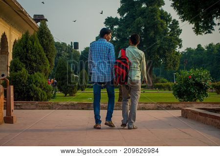 DELHI, INDIA - SEPTEMBER 25 2017: Unidentified gay couple holding their hands and walking around Inlaid marble, columns and arches, Hall of Private Audience or Diwan I Khas at the Lal Qila or Red Fort in Delhi, India, fish eye effect.