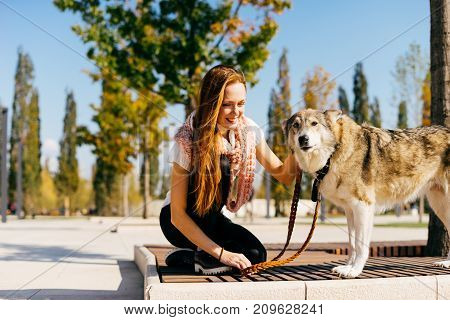 lovely red-haired girl sitting on a bench with her dog in a beautiful park. Good sunny weather.