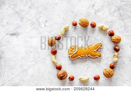 Healthy food for sportsman. Cookies in shape of yoga asanas near nuts on stone table background top view. mock up
