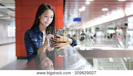 Woman using mobile phone in station