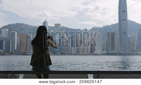 Woman travel in Hong Kong and taking photo with digital camera