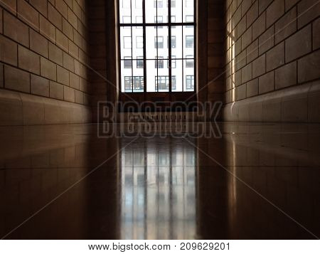 An erie and lonely, yet bright hallway  showcasing a beautiful arched window.