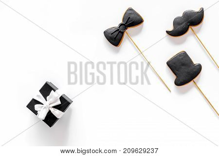 Black tie, mustache and hat cookies on sticks for happy father's day present cookies on white background top view space for text