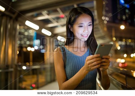 Woman sending sms on smart phone at night