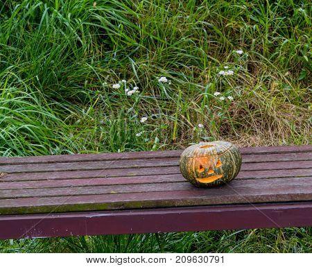 Jack-o-lantern On Wooden Park Bench