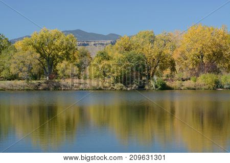 Autumn leaves on lake at Prospect Park in Wheat Ridge Colorado looking towards Golden and Rocky Mountains