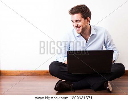 Young man using a laptop while sitting on the floor